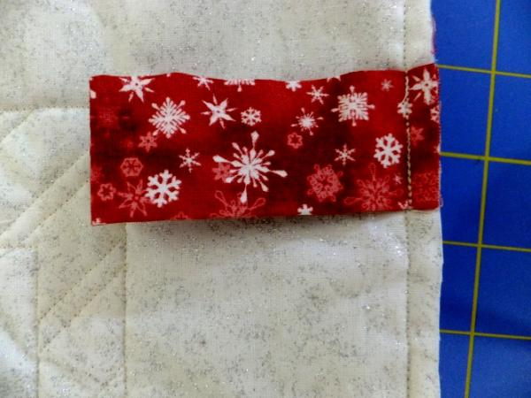 Hanging tab stitched in binding on back of quilt