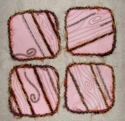 Ruth's four coasters edged with yarn that has been couched in place