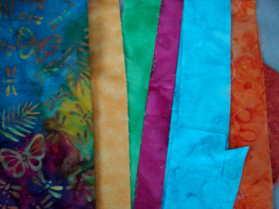 scraps of bright fabric including batiks, yellow, green, pink, blue & orange