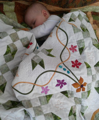 Isabella curled up in Grandmas quilt - Celtic Jewel
